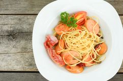 Pasta spaghetti with fried sausage in white plate on wood table background royalty free stock photography