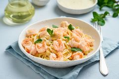 Pasta spaghetti with fried shrimps, bechamel sauce, mint leaf on blue table, italian cuisine, side view.  stock image