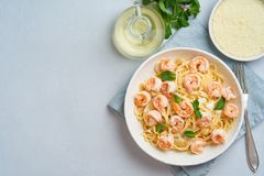 Pasta spaghetti with fried shrimps, bechamel sauce, mint leaf on blue table, top view, copy space, italian cuisine.  royalty free stock image