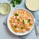 Pasta spaghetti with fried shrimps, bechamel sauce, mint leaf on blue table, top view, italian cuisine.  stock photos