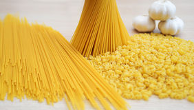 Pasta, spaghetti and garlic. On the table Royalty Free Stock Photos