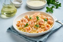 Pasta spaghetti with grilled shrimps, bechamel sauce, mint leaf on blue table, italian cuisine, side view.  royalty free stock images