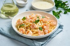 Pasta spaghetti with grilled shrimps, bechamel sauce, mint leaf on blue table, italian cuisine, side view.  royalty free stock photo