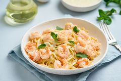 Pasta spaghetti with grilled shrimps, bechamel sauce, mint leaf on blue table, italian cuisine, side view.  stock photos