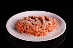 Pasta spaghetti macaroni with parmesan cheese on white plate on black background. Stock Image