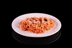 Pasta spaghetti macaroni with parmesan cheese on white plate on black background. Royalty Free Stock Images