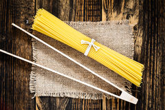 Pasta spaghetti over burlap on wooden table  view from top Stock Photos