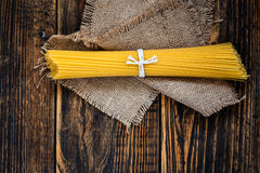 Pasta spaghetti over burlap on wooden table  view from top Stock Photo