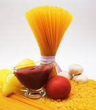Pasta, spaghetti, paper, garlic, tomato and tomato sauce. On the table Royalty Free Stock Image