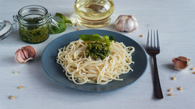 Pasta spaghetti with pesto and ingredients on white wooden background. Royalty Free Stock Photography