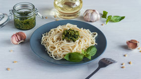 Pasta spaghetti with pesto and ingredients on white wooden background. Stock Photography