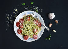 Pasta spaghetti with pesto sauce, basil, garlic, baked cherry-tomatoes Stock Photos
