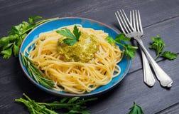 Pasta spaghetti with pesto sauce on blue ceramic plate. Greens for spaghetti rosemary, parsley, lettuce, pesto sauce poured over spaghetti, black wooden royalty free stock image