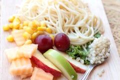 Pasta spaghetti with salad mix fruit. Stock Image