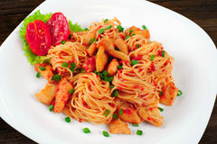 Pasta. Spaghetti with sauce and chicken on a plate. Stock Image