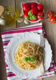 Pasta spaghetti with tomatoes and Basil on a white plate Stock Photo