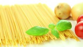 Pasta spaghetti tomatoes onion and basil, italian food background. Italian ingredients, tomato garlic pasta spaghetti and basil isolated on white background stock footage
