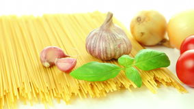 Pasta spaghetti tomatoes onion garlic and basil, italian food background. Italian ingredients, tomato garlic pasta spaghetti and basil isolated on white stock footage
