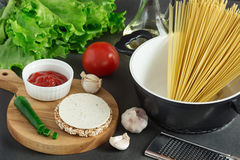 Pasta spaghetti, vegetables and spices on grey background. Pasta spaghetti, cheese loaves with olive oil and vegetables Stock Image