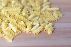 Pasta sparsa sotto forma di spirale sui precedenti di legno Fotografia Stock