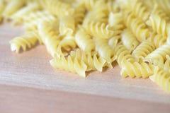 Pasta sparsa sotto forma di spirale sui precedenti di legno Fotografie Stock Libere da Diritti