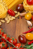 Pasta, spices and cherry tomatoes on a wooden board Royalty Free Stock Photos