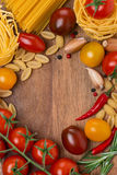 Pasta, spices and cherry tomatoes on wooden board Stock Photo