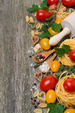 Pasta, spices, herbs and tomatoes on a wooden background Royalty Free Stock Photo