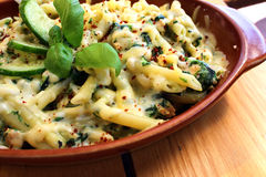 Pasta with spinach. Backed pasta with spinach on the wood table Royalty Free Stock Images