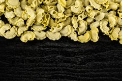 Fresh raw Spinach pasta Creste di Gallo on black wood. Pasta spinach creste di gallo flatlay isolated on black wood background top view raw Royalty Free Stock Photography