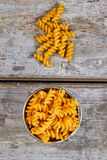 Pasta spiral shape in a metal bucket. Pasta spiral shape in a metal bucket in the old background Royalty Free Stock Images