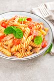 Pasta spirali stirred with fried pieces of chicken, cherry tomatoes Stock Photography
