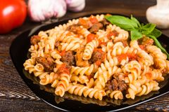 Pasta spirals pasta Bolognese. Tagliatelle with minced meat. On a black plate on a dark wooden background royalty free stock images