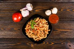 Pasta spirals pasta Bolognese. Tagliatelle with minced meat. On a black plate on a dark wooden background royalty free stock image