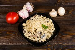 Pasta spirals pasta with mushrooms. Tagliatelle with champig. Nons in creamy sauce on a black plate on a dark wooden background stock photos