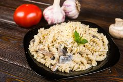 Pasta spirals pasta with mushrooms. Tagliatelle with champig. Nons in creamy sauce on a black plate on a dark wooden background royalty free stock image