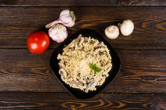 Pasta spirals pasta with mushrooms. Tagliatelle with champig. Nons in creamy sauce on a black plate on a dark wooden background royalty free stock photo