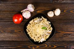 Pasta spirals pasta with red salmon fish and seafood on a blac. K plate on a dark wooden background stock images