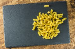 Pasta spirals top view on the background of slate. Pasta spirals top view on a background of slate on the left place for text Stock Images