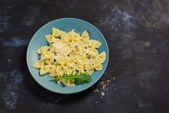 Pasta sprinkled with cheese served on a blue plate. Stock Image