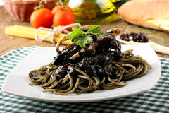 Pasta with squid ink and fresh tomatoes. On complex background Royalty Free Stock Image