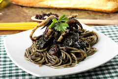 Pasta with squid ink and fresh tomatoes Stock Image