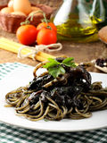 Pasta with squid ink and fresh tomatoes Royalty Free Stock Photos