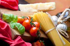 Pasta Still Life. Raw pasta with tomato, basill, garlic, Parmesan cheese and olive oil close up Stock Photo