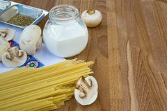 Pasta still-life. With spaghetti, cream and mushrooms Stock Images