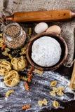 Pasta su fondo di legno scuro con la macro del primo piano della pasta, delle uova, del petrolio e della farina Fotografie Stock