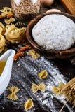 Pasta su fondo di legno scuro con la macro del primo piano della pasta, delle uova, del petrolio e della farina Immagini Stock