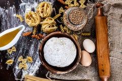 Pasta su fondo di legno scuro con la macro del primo piano della pasta, delle uova, del petrolio e della farina Immagine Stock