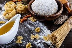 Pasta su fondo di legno scuro con la macro del primo piano della pasta, delle uova, del petrolio e della farina Fotografia Stock