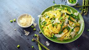 Pasta tagliatelle with asparagus, peas, beans and parmesan cheese on top. healthy food.  royalty free stock photography